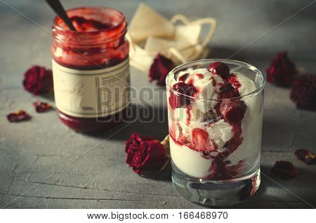 Sundae Ice cream with cherry in chocolate topping, and dried rose flowers on dark background. Love, Valentine's day concept. Copy space, toned