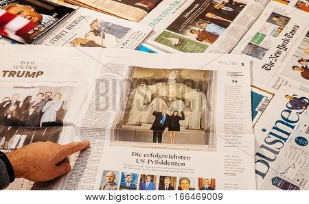 PARIS FRANCE - JAN 21 2017: Man pointing above major international newspaper journalism featuring headlines with Donald Trump and Melania Trump inauguration at Lincoln Memorial as the 45th President of the United States in Washington D.C