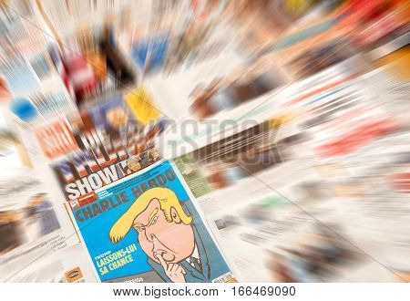 PARIS FRANCE - JAN 21 2017: Charlie Hebdo focus to and major international newspaper journalism featuring headlines with Donald Trump inauguration as the 45th President of the United States in Washington D.C
