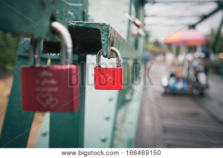 Close focus on aged red lock with two hearts locked on green wall of old bridge. People come to hang lock for forever love.