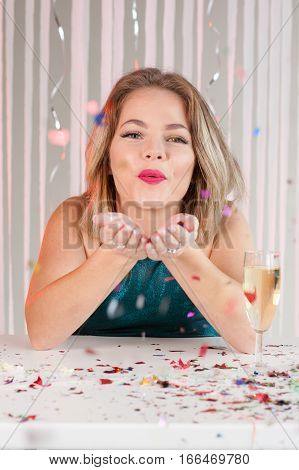 Happy Girl Blowing Colourful Glitter At A Party