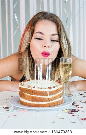 Pretty Girl Looking At Lit Candles On Birthday Cake For Celebration