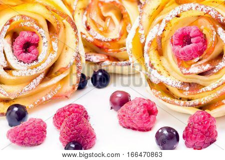 three apple muffins with raspberries and blueberries on a white plate