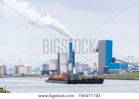 ROTTERDAM NETHERLANDS - MAY 14 2016: Container ship with large industrial complex in the background on the rotterdam Maasvlakte the entrance of the Port of Rotterdam