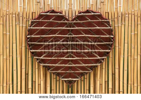 Woven red wooden handmade heart on a brown bamboo wall