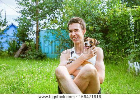 Happy teenager hugging favorite dog breed Jack Russell Terrier. Love to pet.