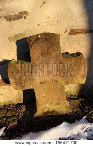 Verwittertes Natursteinkreuz  in der Wintersonne  im Hintergrund alte Kirchenmauer
