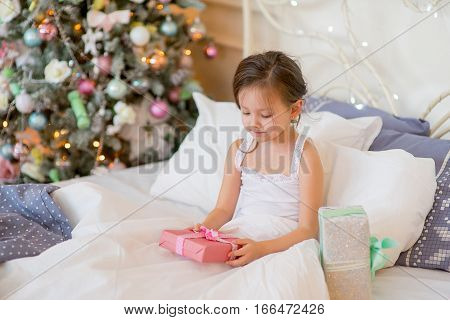 Child girl wake up in her bed near decorated Christmas tree in beautiful room in the holiday morning, enjoying with presents