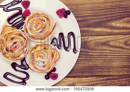 three apple muffins with raspberries and  blueberries, drizzled with chocolate sauce leaving a zigzag trail on a white plate on a wooden background