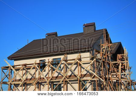 Painting and Plastering Exterior House Scaffolding Facade Wall with New Metal Roofing Outdoor.