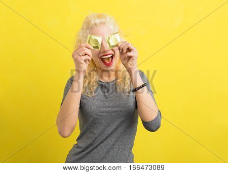Woman holding condoms to cover her eyes