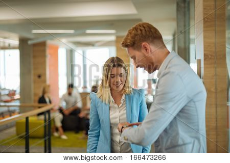 Two happy colleagues working together in a modern office.