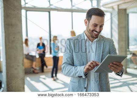 Handsome elegtant businessman working on a tablet.