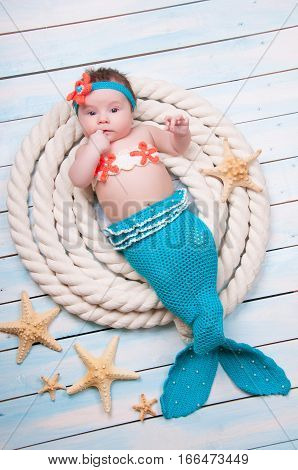 The newborn girl in a mermaid costume, lies in the ropes on wooden boards