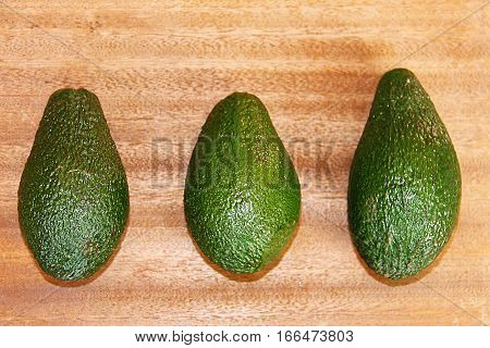 Three green avocados on a wooden background.