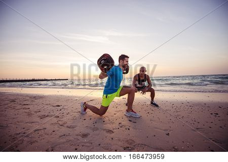 Man doing squats with his life coach at sunrise beach.