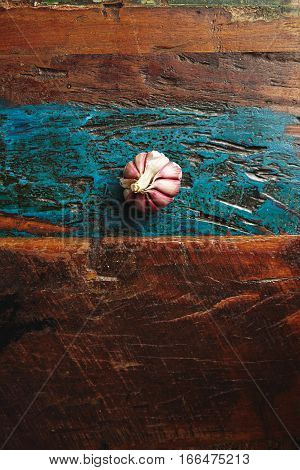 Peeled wild garlic head isolated on rustic aged wooden table or floor