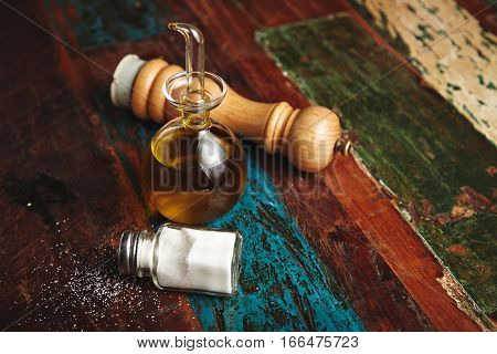 Wooden pepper grinder and sea salt in vintage jar lying on distressed wooden table next to small glass dispencer with virgin extra olive oil inside
