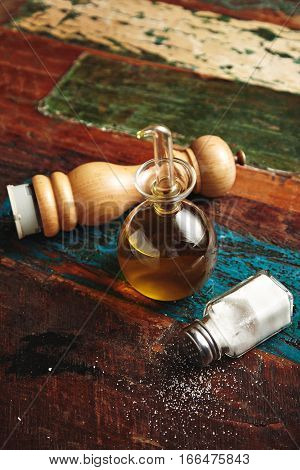 Wooden pepper grinder and sea salt in vintage jar lying on aged wooden sorface of table or floor next to small transparent dispencer with virgin extra olive oil inside, vertical shot