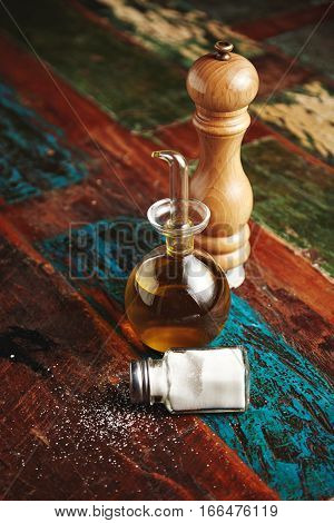 Wooden pepper grinder next to small glass dispencer with virgin extra olive oil inside stands near lying vitage jar with white sea salt, all isolated on aged brushed wooden table , vertical shot