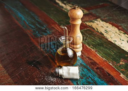 Wooden pepper grinder next to small glass dispencer with dark virgin extra olive oil inside stands near lying vitage jar with white sea salt, all isolated on center of distressed wooden table