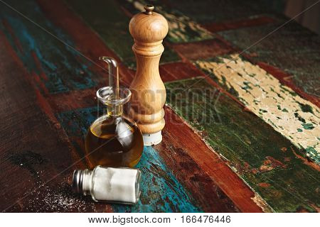 Wooden pepper grinder next to small glass dispencer with dark virgin extra olive oil inside stands near lying vitage jar with white sea salt, all isolated on side of rustic wooden surface