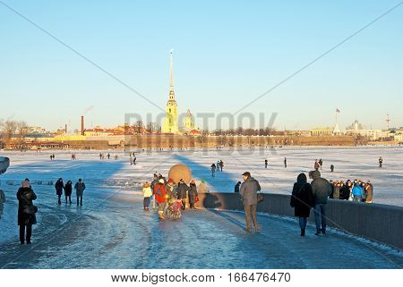 SAINT-PETERSBURG, RUSSIA, JANUARY 21, 2017: People walk on the Neva River ice and on The Old Saint Petersburg Stock Exchange and Rostral Columns. On the background is Saints Peter and Paul Fortress