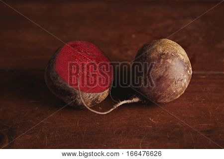 Juicy beetroot isolated on center on rustic wooden table next to half splitted another beetroot