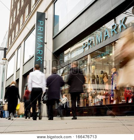 LONDON UK - 23 NOVEMBER 2011: Blurred shoppers walking past the shop front to the Primark store a fashion retailer on London's Oxford Street.