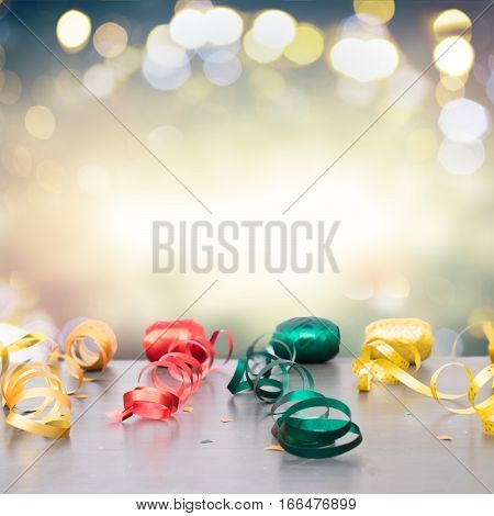 Carnaval festive curling paper decorations on dark wood border with copy space on bokeh festive background