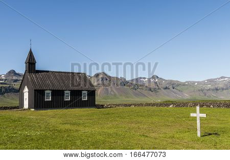 Black wooden Budakirkja at Saefellsnes with cementery and cross on Iceland.