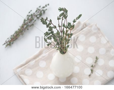 Bunch of thyme sprigs in small white vase over white wooden background. Selective focus on the sprigs.