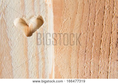 the shape of heart carved on the wooden whetstone as a background