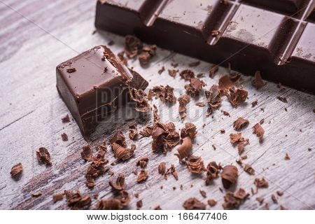 brick of dark chocolate with crumb on wooden desk, macro