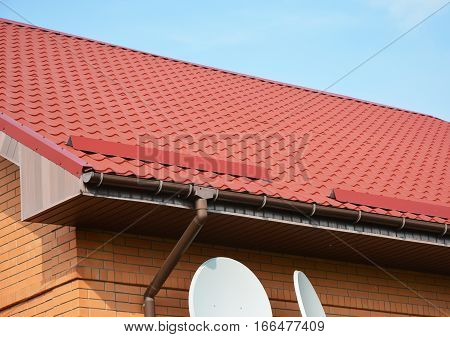 Closeup on new rain gutter system and roof protection from snow board. Red Roofing Construction.