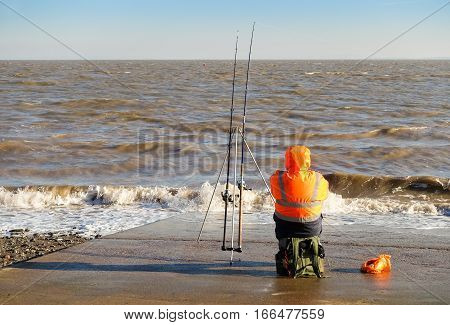 Penarth Vale of Glamorgan United Kingdom - January 22 2017: Angler fisherman sitting on the slipway in Penarth (near Cardiff) in winter fishing in the sea.