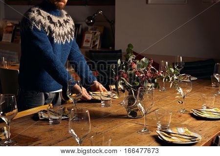 Unrecognizable man in warm knitted ugly sweater serves old vintage rustic wooden table for christmas holiday dinner