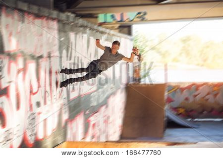 Young man on inline skates. Rollerblader riding on wall. Defy the gravity.
