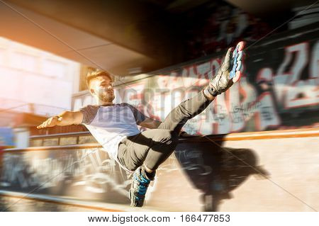 Guy on rollerblades doing trick. Young rollerblader outdoor. Speed and balance.