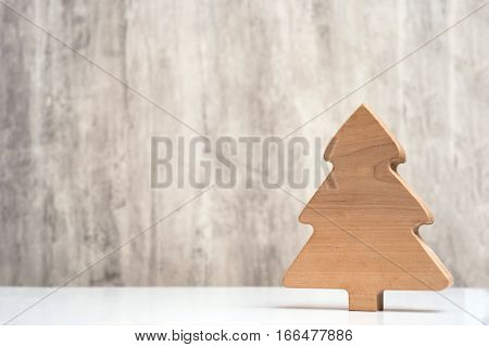 Wooden Christmas tree on grey wood background. Focus on tree