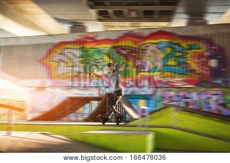Young man on rollerblades. Rollerblader in skatepark. Skills of extreme sportsman.