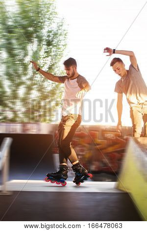 Young people rollerblading. Two guys outdoor. Friends in skate park.