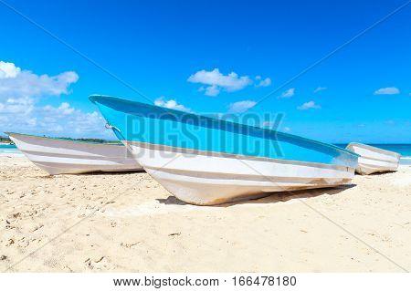 Blue white pleasure boats lay on sand of Macao Beach coastal landscape. Dominican Republic Hispaniola Island poster