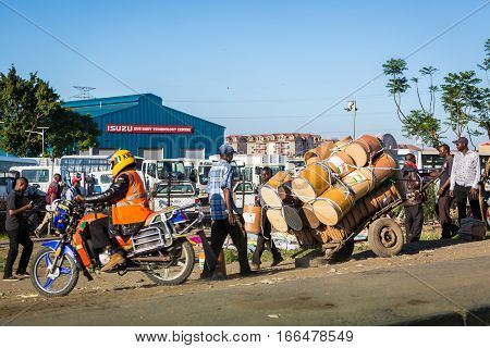 Nairobi Kenya - December 9 2016: Taxi motorcycle and barrels for clean water