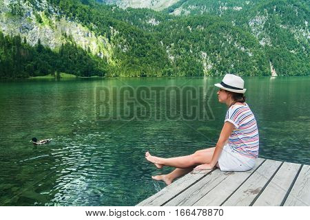 Young beautiful girl sitting on a pier by Konigssee lake with clear green water and duck swimming in it. Berchtesgaden National Park Bavaria Germany