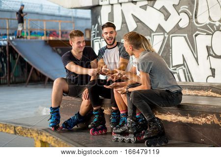 People playing rock paper scissors. Guys on inline skates sitting. Guess or react.