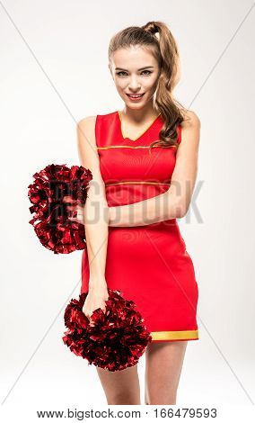 Smiling cheerleader posing with pom-poms and looking at camera on grey