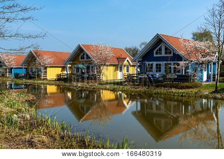 Wooden bungalows and garden on campsite in spring