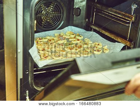 Christmas cookies are being baked in oven. Cooker opens a door of the oven to check readiness of the cookies