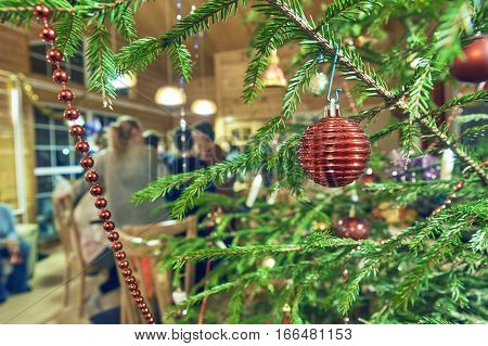 Big company of friends celebrate Christmas in beautiful country house.Decorated Christmas tree on the foreground and people on the blurred background.